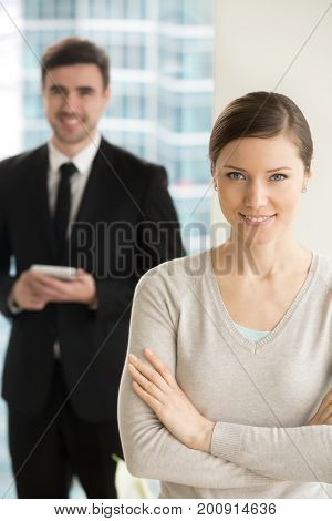 Beautiful smiling businesswoman looking at camera, happy smm manager posing with arms crossed, businessman holding tablet smartphone at background, internet online digital marketing team portrait