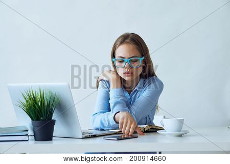 Young woman in blue glasses working at computer in office.