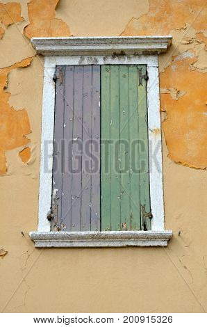 old window in green and purple with orange wall