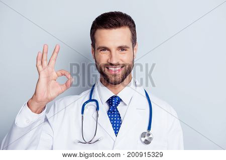 Handsome Young Bearded Intern Is Showing Ok Sign In A Uniform On White Background Isolated. He Has A