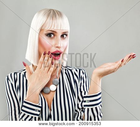 Surprised Fashion Model Woman Showing Empty Copy Space on the Open Hand. Empty Hand Fashion Makeup Blonde Bob Hairstyle Fashion Cloth