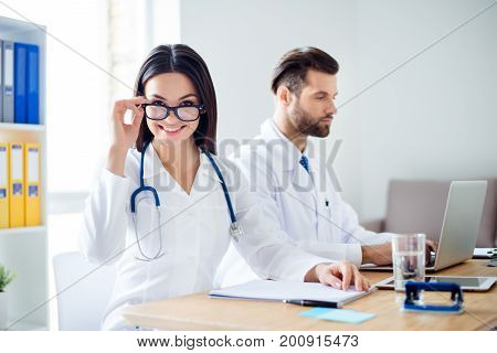 Young Attractive Brunette Nurse Is Fixing Her Glasses And Smiling. Her Colleague Is A Young Stylish