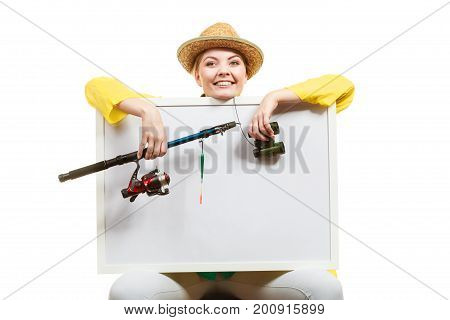 Fishery spinning equipment angling sport and activity concept. Happy woman with fishing rod holding blank white board with copyspace.