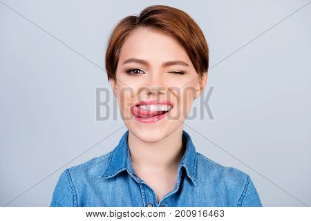 Close Up Portrait Of Happy Pretty Young Girl With Short Hair And Jeans Shirt Licking Lips And Giving