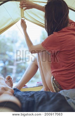 view from inside a tent at the forest and woman emerge from tent. travel and hiking concept, Tourist tent inside with people