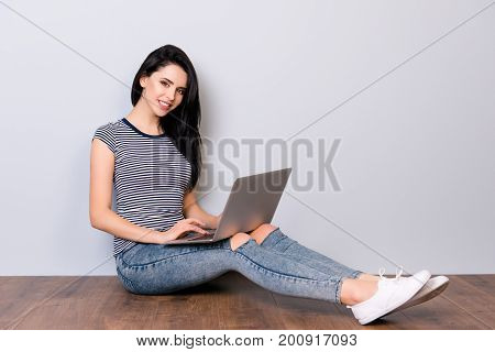 Horizontal Photo Of Young Smiling Cute Lady Sitting On The Floor  With Laptop On Her Knees And Typin