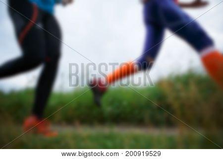 Defocused image from below of two running sportswomen in park