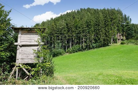 Wooden deer stand along the edge of a meadow, horizontal view. Tree or box stand. Enclosed platform. Elevates the hunter for better vantage point, keeps him hidden. Heuberg, Salzburg, Austria. Photo.