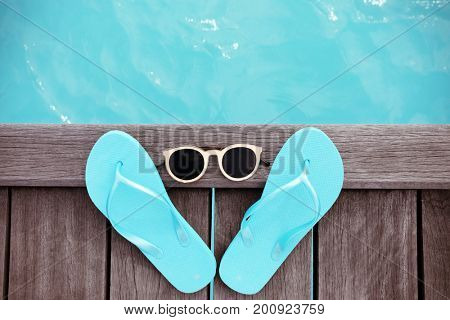 Flip-flops and sunglasses on wooden pontoon at sea resort. Summer vacation concept
