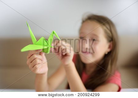 The girl puts origami from paper. Lesson of origami