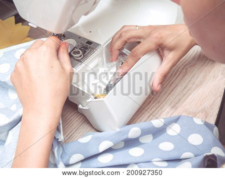 Female Hands Sew The Blue Fabric
