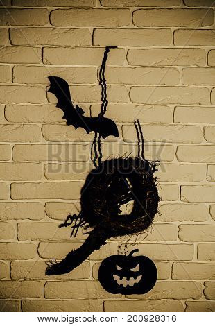 Halloween black bat pumpkin and nest silhouette paper cutouts on beige brick wall. Holiday celebration symbols. Mystery and superstition concept.