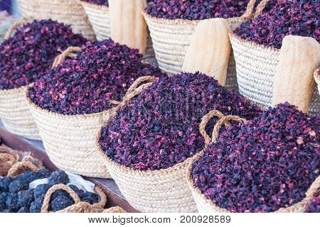 Hibiscus dry herb in baskets. Natural organic herbs. Hibiscus lilac flowers in baskets. Condiment and ingredient concept. Arabic herbs on traditional bazaar.