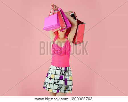 Woman with shopping bags. Fashion shopper posing on pink background. Holidays celebration concept. Sale and black friday. Girl wearing fashionable clothes.