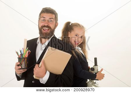 Kid and dad hold microscope book and stationery. Girl and man in suit and uniform. Father and schoolgirl with cheerful faces isolated on white background. Home schooling and back to school concept