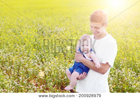 Young happy smiling father with his infant son at canola field