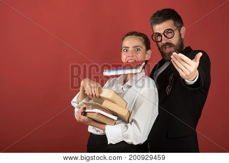 Back to school concept. Girl and bearded man in suit. Teacher and schoolgirl with enthusiastic faces on terracotta background. Teenager and tutor with glasses hold pile of books and book in teeth