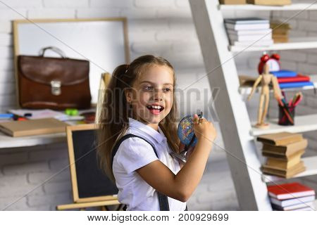 Schoolgirl Holds Little Globe On Light Brick Wall Classroom Background