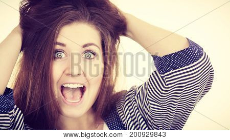 Attractive woman with dark brown hair having shocked amazed face expression with wide open mouth touching her hair