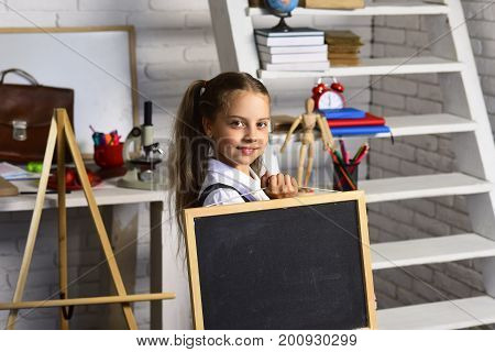 Schoolgirl Holds Chalkboard On Light Brick Wall Classroom Background