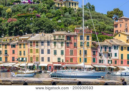 PORTOFINO, ITALY - JUNE 26, 2017: Beautiful daylight view to ships on water and buildings in Portofino city of Italy. Tourists walking on sidewalk.