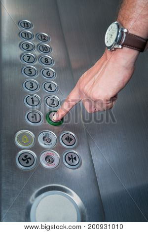 Close up of male forefinger pressing the zero floor button in the elevator. Iron made interior.