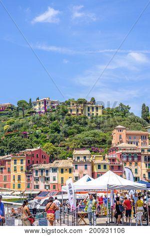 PORTOFINO, ITALY - JUNE 26, 2017: Beautiful daylight view to tourists walking near port of Portofino in Italy