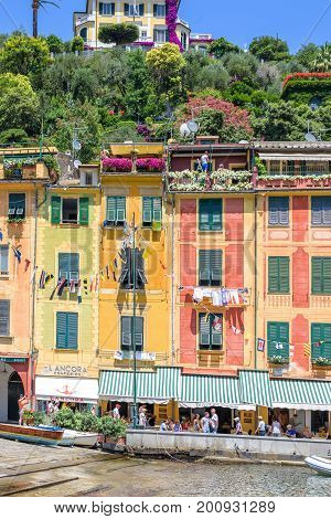 PORTOFINO, ITALY - JUNE 26, 2017: Daylight beautiful view to Portofino, Italy buildings with people walking and shopping on sidewalk.