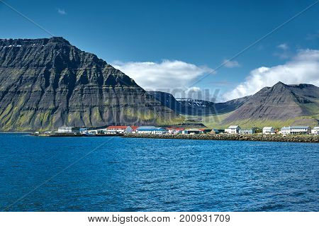 Travel to Iceland. beautiful sunrise over the ocean and fjord in Iceland. Icelandic landscape with mountains, sky and clouds. View of Flateyri, a village in the north-west of Iceland, on the Westfirdir peninsula