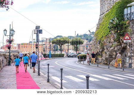 SANTA MARGHERITA LIGURE, ITALY - JUNE 27, 2017: Beautiful daylight view to Santa Margherita Ligure city road in Italy. People walking on sidewalk. Mountains and blue sky background.