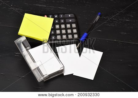 Pen, Notes, Business Card Holder And Calculator On Office Table