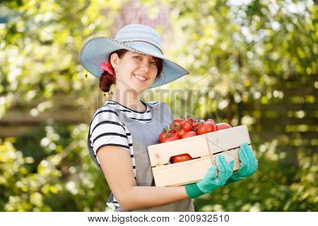 Woman in hat with tomato