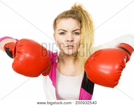 Sporty angry and agressive woman wearing red boxing gloves fighting. Studio shot on white background.