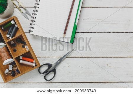 Top view accessories tailor concept.Tailored tools is cutting scissors spools of thread buttons and sewing clothes. Notebook for free space text on rustic wooden background.fashion concept.flat lay.