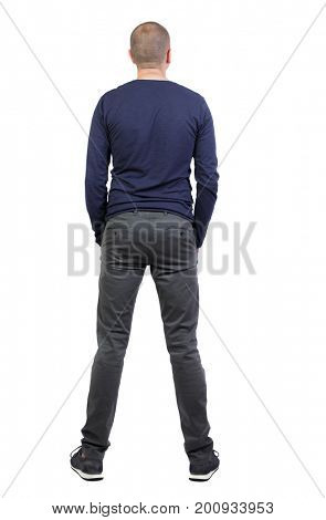Back view of man in trousers. Standing young guy. Rear view people collection.  backside view of person.  Isolated over white background. A man in black pants and sneakers is standing and looking up