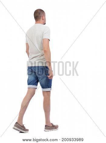 Back view of going  handsome man in shorts. walking young guy . Rear view people collection.  backside view of person.  Isolated over white background. The guy in the denim shorts goes sideways.
