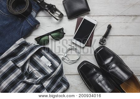 Top view accessories to travel with man clothing concept. shirt jean mobile phone on wooden background.watch sunglasses and shoes on wood table.
