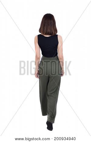 back view walking  woman in pants. beautiful girl in motion. backside view of person.  Rear view people collection. Isolated over white background. Top view of girl in green trousers passing forward