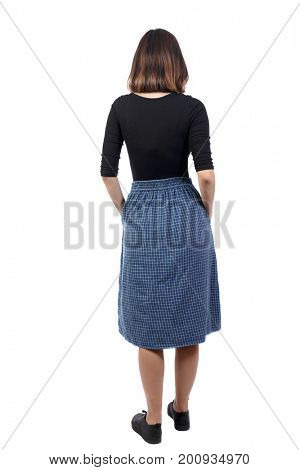 back view of standing young beautiful  woman. girl  watching. Rear view people collection.  backside view of person. girl in a blue skirt is thrust her hands into her pockets and looks in front of her