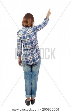 Back view of  pointing woman. beautiful girl. Rear view people collection.  backside view of person.  Isolated over white background. A girl in a plaid shirt shows a hand up.