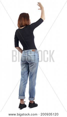Back view of beautiful woman welcomes. Young teenager girl in jeans hand waving from. Isolated over white background. The girl in jeans and a black T-shirt is standing sideways and waving her hand.