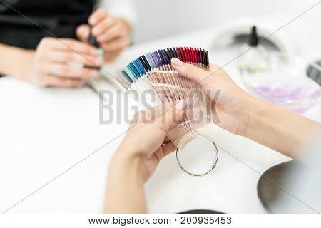 Woman Choosing Nail Polish Color