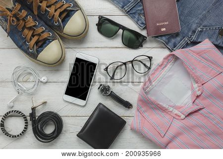 Top view or Flat lay of accessory to travel with fashion women clothing background concept.Essential items for teenage or adult to traveler. Mix object on modern rustic white wooden office desk.