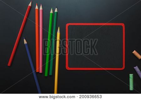 Top view back to school concept and education background concept.backboard and chalk board with stationery office beautiful color pencil on black table.office supply.