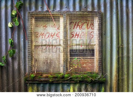 A boarded and secured window in an old corrugated tin shed