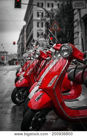 Red mopeds ares staying in the line at the street