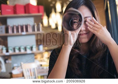 A beautiful Asian woman roll a book and looking through it with one eye while closing another eye with feeling happy sitting in cafe