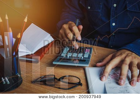 Asian man accountant or banker calculate finances / savings money or economy concept.Idea for save coin and accounting. Essential accessories on table office desk.Sun flare light.