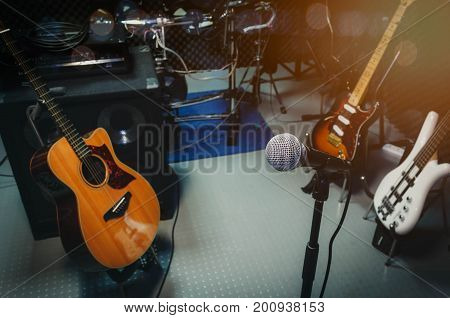 instrument rock music / musical band at home audio record room / studio recording. Equipment this event the microphone acoustic and electric guitar bass electronic drum and sound audio control panel.