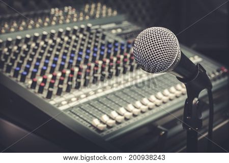 The producer music or musician equipment concept.Selective focus of single microphone with sound music mixer at the recording studio room.Vintage tone design background.